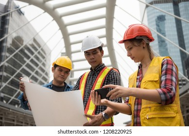 Construction engineer team check project plan from paper blueprint and smartphone in town. International joint venture to work in city for real estate constructed building.