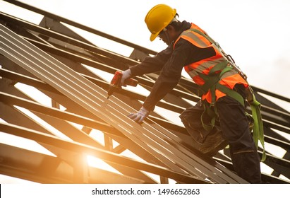 Construction engineer wear safety uniform using an electric drill and screw tools to fasten down metal roofing work for roof industrial concept with copy space