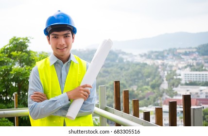 A construction engineer. Wearing a helmet and vest holding a roll of plans with blur city or building background in construction concept