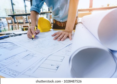Construction engineer working at blueprint to build large commercial buildings in office. Engineering tools and construction concept.