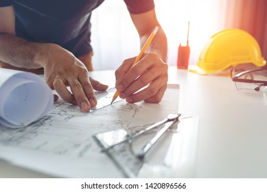 Construction engineer working at blueprint to build large commercial buildings at home