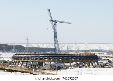 Construction engineering project with cranes. Winter building work. Urban industrial landscape.