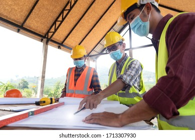 The construction engineering team, a group of engineers and architects put on a protective mask, talk to each other on the table with a drawing / blueprint, wear a helmet used for industrial.