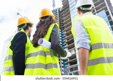 Construction engineers or architects at building site of highrise building