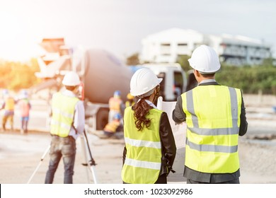 Construction engineers discussion with architects at construction site.