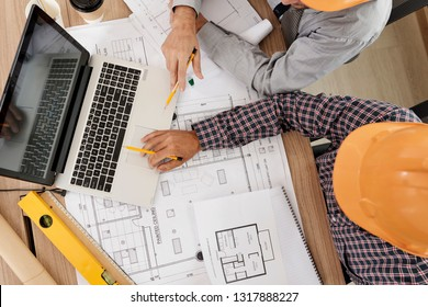 Construction engineers gathered at laptop able covered with paper blueprints to discuss project