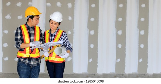 Construction engineers of man and woman or architect are working, designing,planing,discussion for new project and management business plan  blueprint in hand at construction site. Industrial concept.