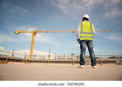 Construction engineers supervising progress of construction project stand on new concrete floor top roof and crane background