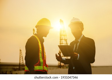 Construction engineers use tablet communications against building construction site backgrounds in the morning.