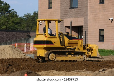 Construction Equipment moving Soil at Building Site