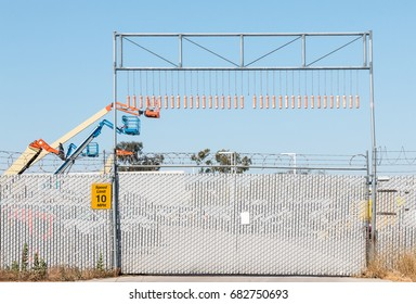Construction equipment security fence and barbed wire. Hydraulic crane cherry picker vehicles in background. Blue sky.