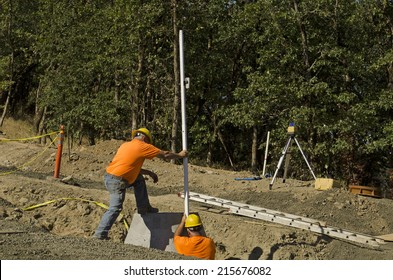 Construction excavation contractor uses a level rod and laser to install a concrete sewer vault structure
