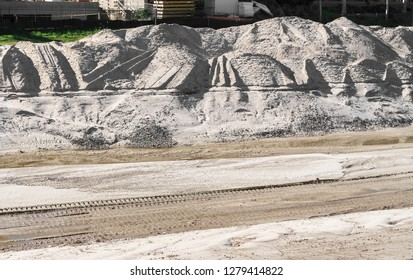 Construction excavation site with mounds of dirt and tire tread tracks in mud.