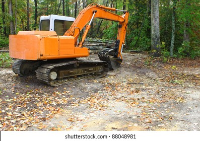 A construction Excavator used for excavating of trees debris and anything else needed resting on the ground outside in the woods with room for your text.