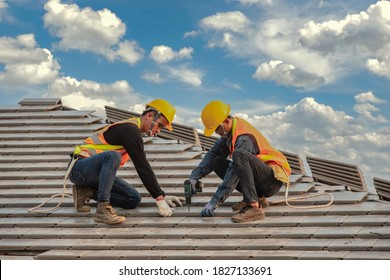 Construction Experience technician wearing safety harness belt working on roof structure building on construction site Roofer using air pneumatic nail gun and installing concrete roof tile on roof top