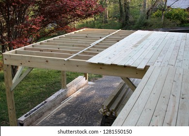 Construction of an exterior wooden deck in springtime with the framing done and boards nailed down across half of it creating a platform.