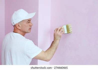 Construction finisher in white clothes covers the walls pink decorative plaster