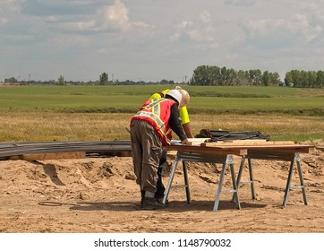 A construction foreman and superintendent review the construction plans on a makeshift table of plywood on a construction project to insure compliance and conformity to the quality of the project