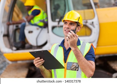 construction foreman talking on walkie-talkie holding clipboard