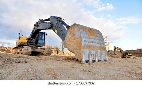 Construction of foundation excavator works in sand pit. Groundworks, site levelling, construction of reinforced ground beams on piled foundations at construction site. Earth-moving heavy equipment