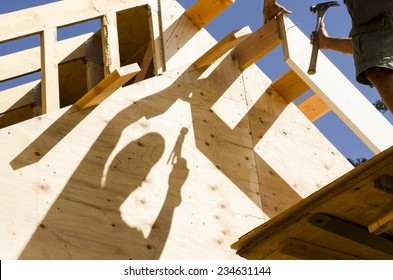 Construction framing contractor carpenter building out the gable end of the roof with purlin and facia trim boards