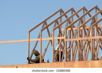Construction framing contractor installing the roof truss system to a new commercial residential development