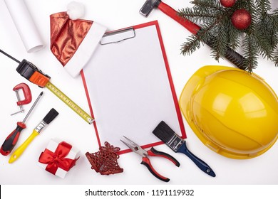 Construction hard hat, tools, blank clipboard, gifts, fir tree branches and Christmas decoration on a white background. Top view with copy spase. New Year and Christmas. Construction concept.