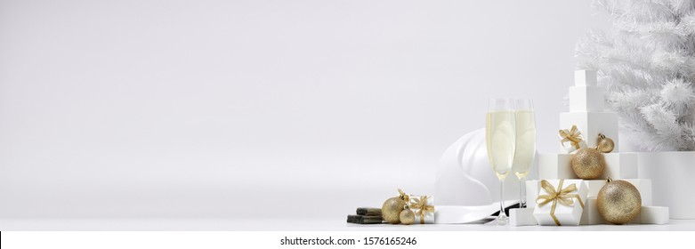 Construction hard hat, white fir tree, two glasses with champagne, gift boxes and Christmas ornaments on a white background with copy space. New Year and Christmas construction background