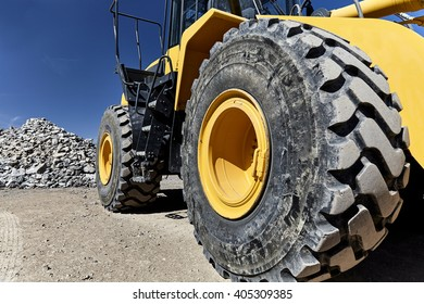 Construction heavy equipment loader and bucket on jobsite with gravel and rocks