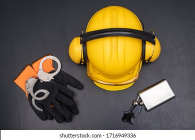 Construction helmet, handcuffs and vodka in a bottle. Drunkenness at work in the responsible position of engineer. Dark background.