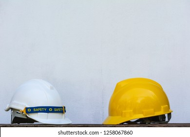 Construction Helmet, yellow and white safety helmet on wooden table.
