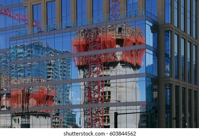 Construction of a high rise building reflected in the glass façade of another building