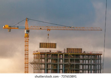 Construction of a high-rise building with a crane. Building construction using formwork. The construction crane and the building against the blue sky.