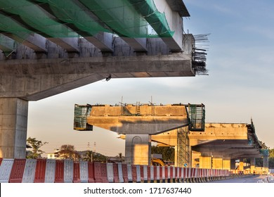 Construction of highway overpass bridge infrastructure in progress with morning sun rays in Malaysia