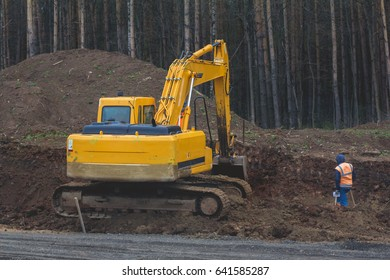 Construction of the highway - yellow excavator at work