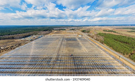 Construction of industrial greenhouses aerial view under blue cloudy sky. Feeding the planet, feeding people.