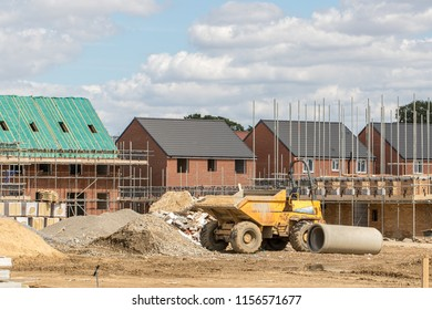Construction industry. Building new homes on a new housing estate. Unfinished buildings on a building site at various stages of completion. With scaffold, a dumper truck and drainage pipe.