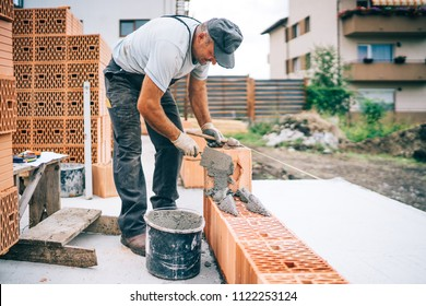 Construction industry details - Worker mason building exterior brick walls