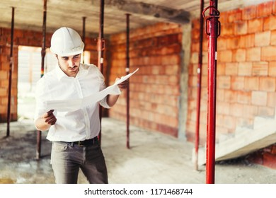 Construction industry engineer working on house building site - reading paper plans and coordinating workers