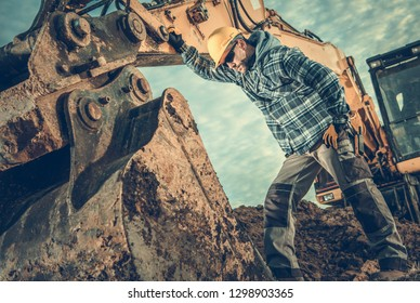 Construction Industry. Heavy Equipment Operator Job. Excavator and Caucasian Worker in Hard Hat. Men Looking Inside Excavator Bucket.