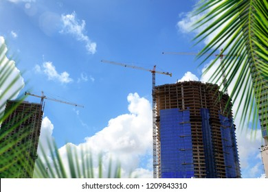 Construction industry image of tall cranes and building exterior in construction site over sunny sky in Florida, USA