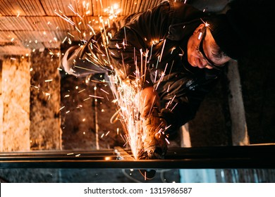 construction industry middle aged man working on cutting iron bars, steel bars with angle grinder using safety equipment