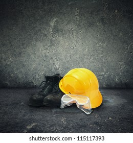 Construction industry safety equipment. Yellow hard hat, black boots and plastic protective goggles.
