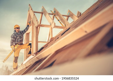 Thema Bauindustrie. In seinen 40er Jahren arbeitet der kaukasische Vertragspartner mit einem Sprit Level Tool in seiner Hand auf dem Dach der neu gebauten Holzhausstruktur.