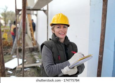 Construction inspector examine styrofoam insulation of house facade