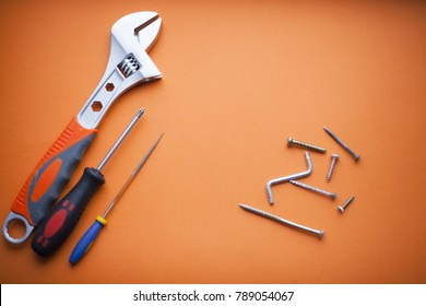 Construction instruments on the orange background. Space for your text. Top view.