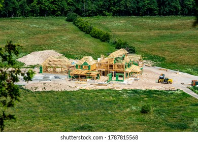 construction of a large wooden house on a green field