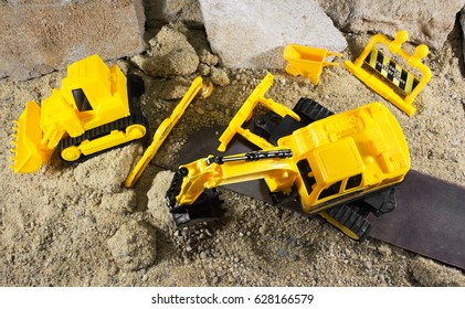 Construction machine toys upper view. Yellow construction machines standing on sandy & rocky surface upper view.