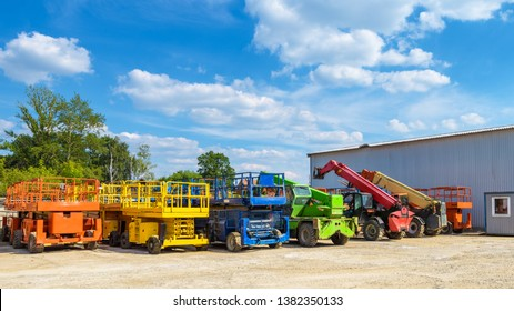 Construction machinery in summer. Colorful vehicles and heavy trucks on the outdoor parking. Panorama of the repair equipment on sunny day. Nice cherry pickers in folded form.
