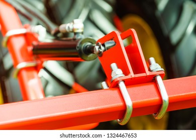 Construction machines concept. Detailed closeup of screw and u bolts on red indrustrial machinery